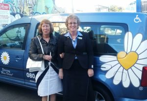 Pam and Lynda are posing for the photo in front of a Driving miss daisy car, about to go into the conference
